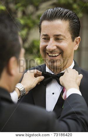 Hispanic man having bowtie adjusted