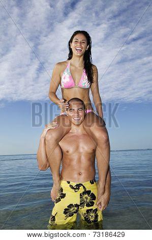 Pacific Islander woman sitting on boyfriend's shoulders