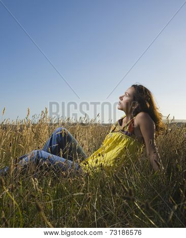 Hispanic woman sitting in field