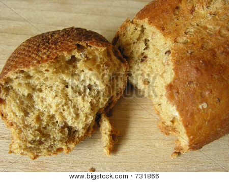 Broken wholemeal bread roll with grains/seeds