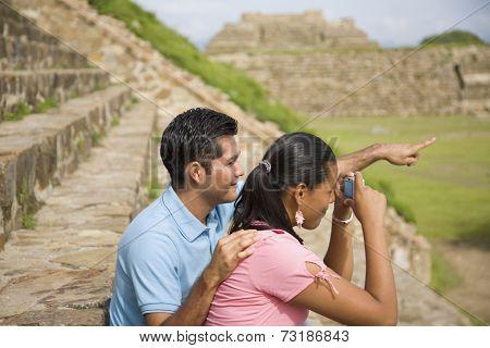 Hispanic couple taking photograph of ruins, Oaxaca, Mexico
