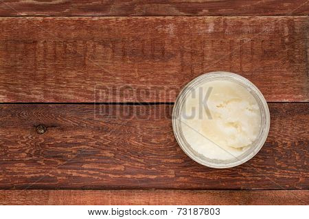 glass jar of coconut cooking oil on grunge red barn wood surface, top view with a copy space