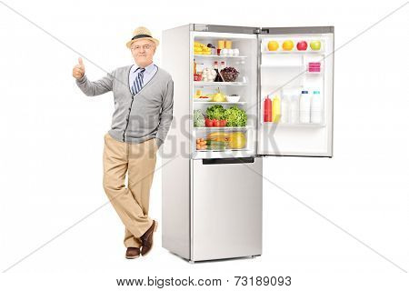 Senior leaning on a fridge and giving thumb up isolated on white background
