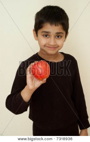 An Handsome Indian Kid Holding Apple