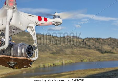 FORT COLLINS, CO, USA, September 30 2014:  Radio controlled DJI Phantom quadcopter drone with Panasonic Lumix GM1 camera (home made mount) is flying over Pineridge Natural Area at Colorado foothills.