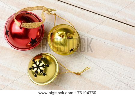 High angle closeup of three jingle bells on a white wood table. Two gold bells and one red in horizontal format with copy space.
