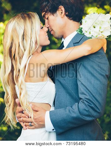 Romantic Wedding Couple Embracing and Kissing