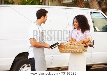 Bakers Using Digital Tablet Unloading Bread From Van