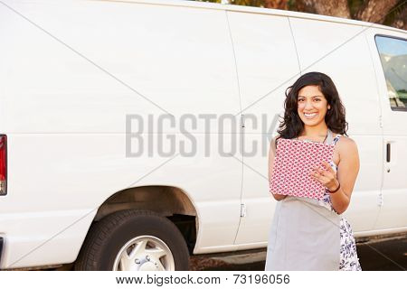 Woman Wearing Apron With Clipboard In Front Of Van