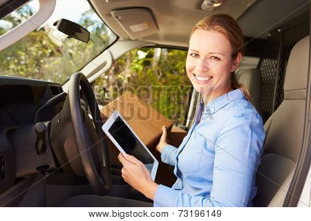 Female Delivery Driver Sitting In Van Using Digital Tablet