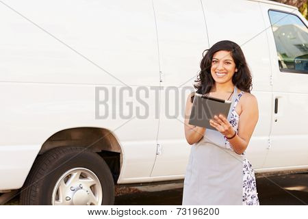 Woman Wearing Apron With Digital Tablet In Front Of Van