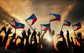 stock photo of filipino  - Group of People Waving Filipino Flags in Back Lit - JPG