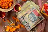 stock photo of pooja  - Indian currency bills with traditional lamp  - JPG