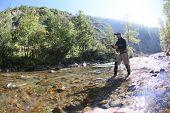 stock photo of fly rod  - Fisherman using flyfishing rod in beautiful river  - JPG