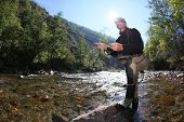 image of fly rod  - Fly fisherman using flyfishing rod in beautiful river  - JPG