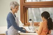 picture of granddaughters  - Hispanic grandmother and granddaughter washing dishes - JPG