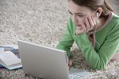 stock photo of pre-adolescent girl  - Young girl lying on the floor with laptop - JPG