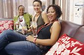 image of chums  - Three women smiling and drinking on sofa - JPG