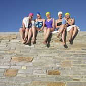 picture of bathing  - Group of senior women in bathing suits sitting on stone wall - JPG