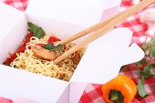 stock photo of chinese checkers  - Chinese noodles and sticks in takeaway box on fabric background - JPG