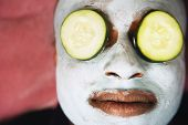 pic of african mask  - African man with facial mask and cucumber slices on eyes - JPG