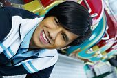 stock photo of carnival ride  - Close up of young Hispanic man smiling next to carnival ride - JPG