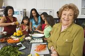stock photo of niece  - Large Hispanic family in kitchen preparing food - JPG