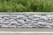 stock photo of sandbag  - Wall of sandbags and tarp for flood protection - JPG