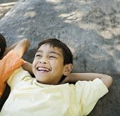 stock photo of chums  - Asian boy laying with arms behind head - JPG