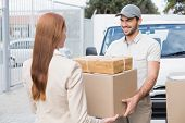 image of shipping receiving  - Delivery driver passing parcels to happy customer outside the warehouse - JPG
