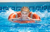 pic of lifeline  - cute little girl swims with a lifeline in the pool in  summer - JPG