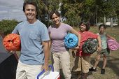 stock photo of sleeping bag  - Hispanic family holding sleeping bags - JPG