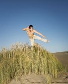 picture of pacific islander ethnicity  - Pacific Islander man jumping on beach - JPG
