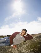 stock photo of pacific islander ethnicity  - Pacific Islander man laying on rock formation - JPG