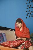 image of middle eastern culture  - Middle Eastern woman typing on laptop - JPG