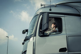 stock photo of truck-stop  - Portrait of a truck driver sitting in cab - JPG