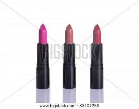 Three lipsticks in glamorous colors, isolated on white background with natural reflection