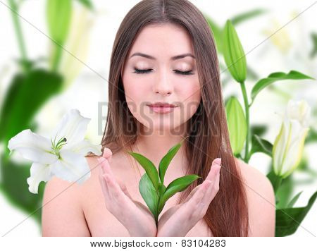 Beautiful young woman holding green leaves on lily flower background