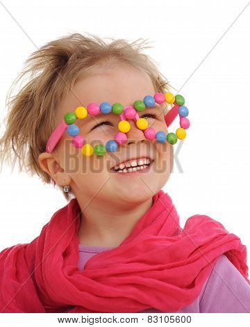 Portrait of cute little girl wearing funny glasses decorated with colorful sweets smarties candies