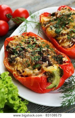 Stuffed red peppers with greens and vegetables on table close up