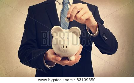 Young Man Depositing Money In Piggy Bank