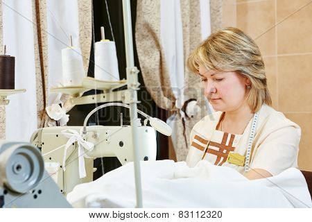 female tailor working with cloth in sewing workshop