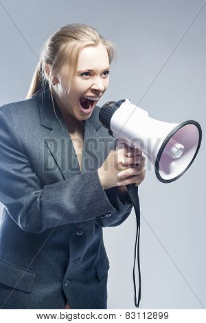 Furious Caucasian Blond Female In Suite Shouting Using Megaphone. Against Gray Background.