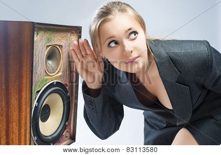 Surprised Caucasian Blond Female Harkens To Outdated Loudspeaker In Studio.