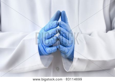 Doctor hands in sterile gloves on background