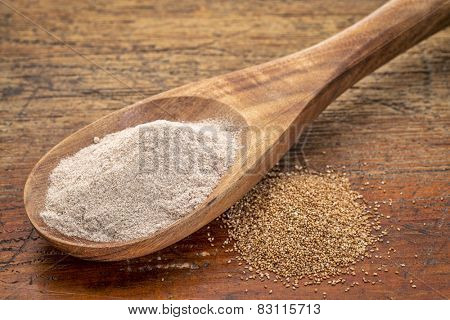teff grain and flour i- a wooden spoon against grained wood background