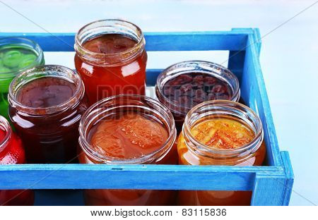 Homemade jars of fruits jam in crate on color wall table background