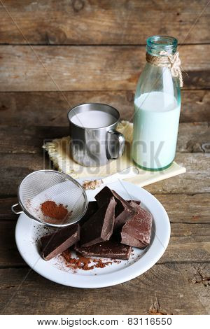Metal mug and glass bottle of milk with chocolate chunks and strainer of cocoa on plate and rustic wooden planks background