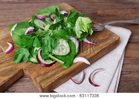 Mix salad leaves with sliced cucumber and onion on cutting board and wooden table background