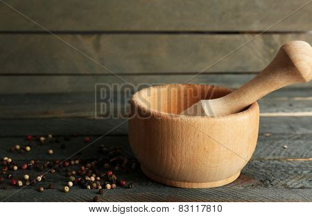 Mixture of peppers in mortar on wooden background